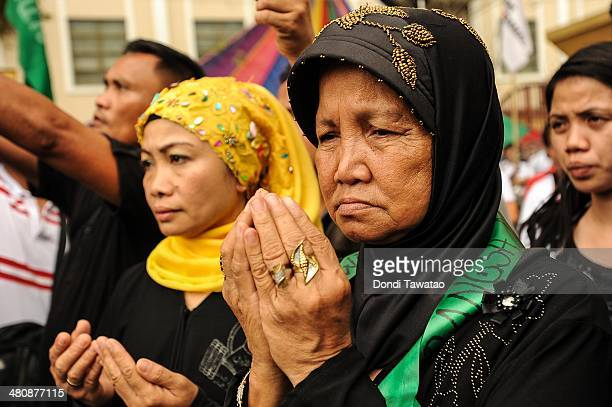 Filipino Muslims pray outside the presidential palace after the conclusion of the signing of the Comprehensive Agreement on the Bangsamoro between...