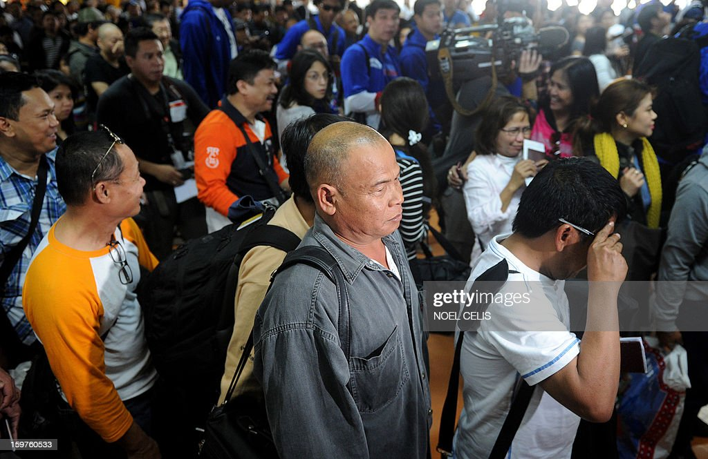 Filipino overseas workers (foreground) arrive at Manila International Airport on January 20, 2013 after being sent home by their employer in Algeria due to security fears following an Islamic militant attack at a remote gas plant. Many of the 39 returnees said they worked for a British energy facility hundreds of kilometres from the In Amenas gas plant that was attacked by the militants last week.