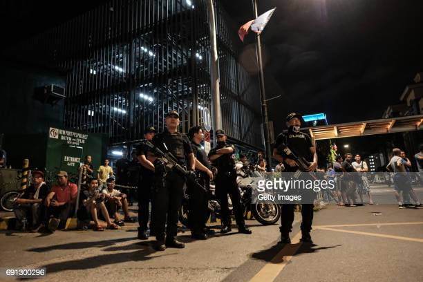 Filipino policemen stand guard outside the Resorts World Manila building after gunshots and explosions were heard in Pasay City on June 2 2017 in...