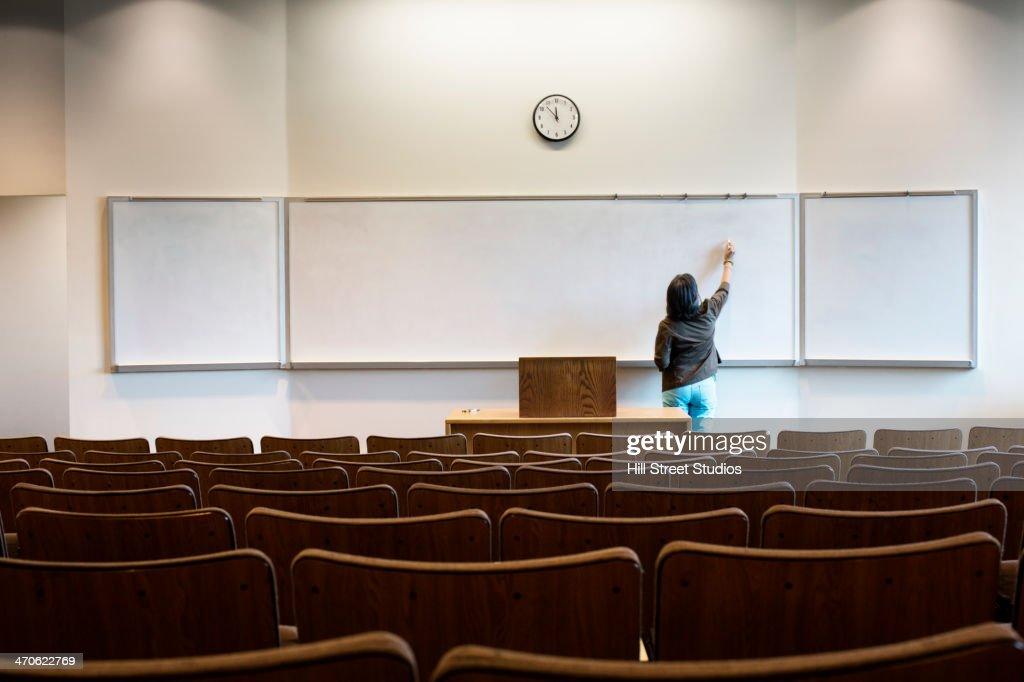 Filipino professor writing on whiteboard in empty lecture hall : Stock Photo