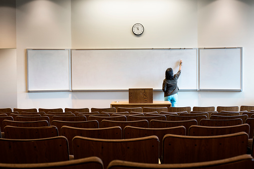Filipino professor writing on whiteboard in empty lecture hall - gettyimageskorea