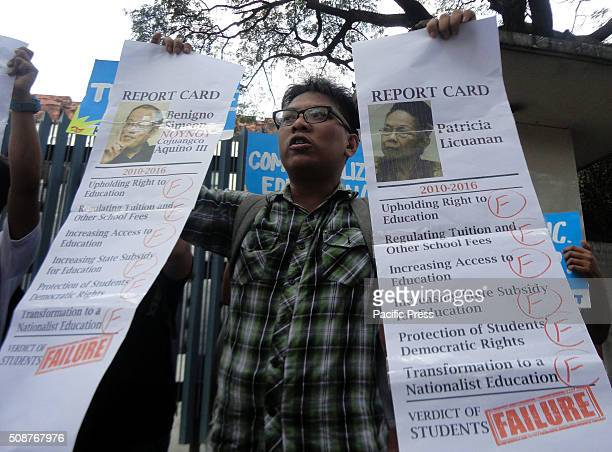 Filipino protester displays mock report cards of Philippine President Benigno Aquino III and Commission on Higher Education commissioner Patricia...