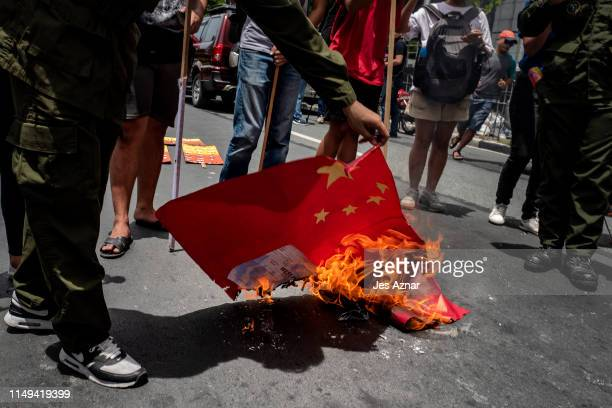 Filipino protesters burn a Chinese flag in front of the Chinese consulate to mark Philippine Independence day on June 12 2019 in the business...