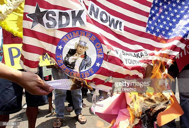 Filipino protesters burn a US flag with a picture of US President George W Bush depicting him as the number one terrorist during an antiwar protest...