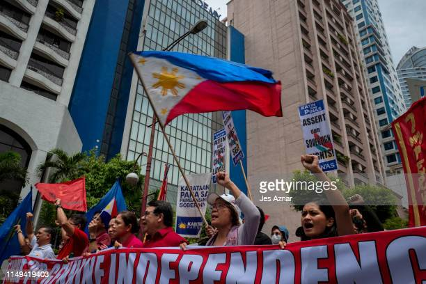 Filipino protesters with Philippine flags march towards the Chinese consulate to mark Philippine Independence day on June 12 2019 in the business...