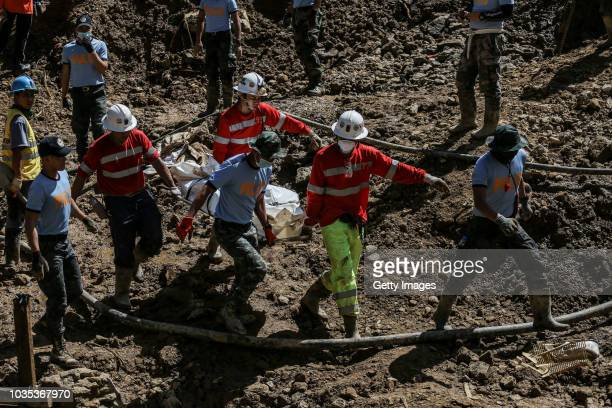 Filipino rescuers carry a body of a person inside a body bag at the site where people were believed to have been buried by a landslide on September...