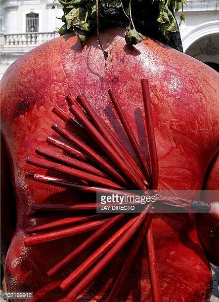 A Filipino Roman Catholic devotee flagellates himself themselves during a ritual for Holy Week on the run up to Easter in San Fernando north of...