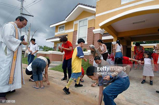 Filipino Roman Catholic priest officiating house blessing rites looks at party guests picking up 'good luck' coins from a family who just moved into...