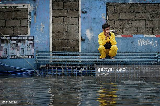 A Filipino sits on railings above a flooded road in Quezon city Metro Manila Philippines July 16 2014 Typhoon Rammasun left at least 12 people killed...