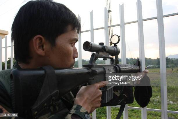 Filipino soldier aims his sniper rifle following reports that apparent members of the Ampatuans rebel group have been seen near the town hall...