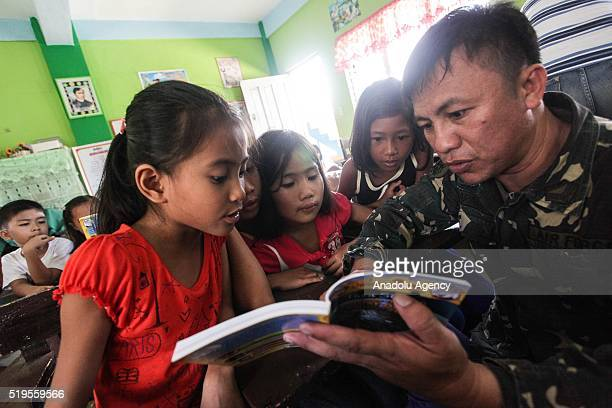 Filipino soldier reads a book to students during My teacher my soldier program wherein Filipino and American soldiers teach and distribute books to...
