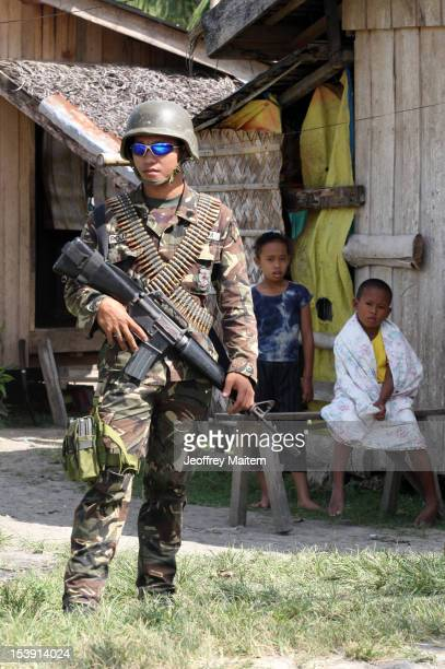 Filipino soldier secures a village along the highway not far from an area where a breakaway faction of the Moro Islamic Liberation Front are armed...