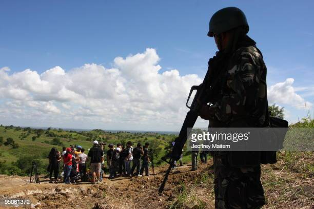 Filipino soldier secures the area after journalists offered flowers prayers and lit candles at the site where 57 people including many journalists...