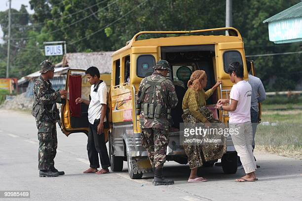 Filipino soldiers inspect vehicles in Shariff Aguak on December 5 in the capital of Maguindanao province as Philippines President Gloria Macapagal...