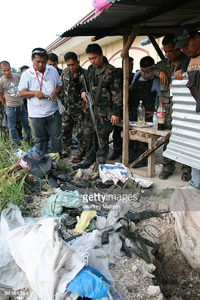 Filipino soldiers look upon seized weapons apparently used in the November 23 massacre which saw 57 people killed at the back of Ampatuan town hall...