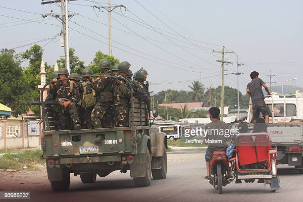 Filipino soldiers on board a humbee patrol along the highway in Shariff Aguak on December 5 in the capital of Maguindanao province as Philippines...