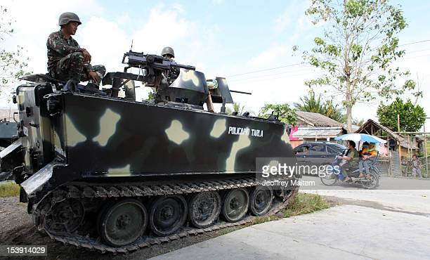 Filipino soldiers secure a village along the highway not far from an area where a breakaway faction of the Moro Islamic Liberation Front are armed...