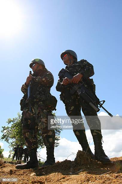 Filipino soldiers secure the area after journalists offered flowers prayers and lit candles at the site where 57 people including many journalists...