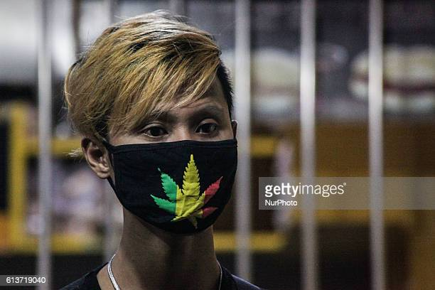 Filipino spectator wearing mask with logo of marijuana observe the crime scene at Pinagbuhatan in Paranaque Manila on 25 September 2016 According to...