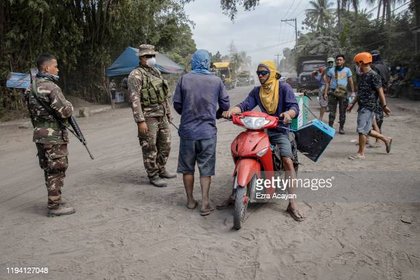 Filipino troops and policemen monitor a checkpoint after residents were briefly allowed to return to their homes to recover their belongings at the...