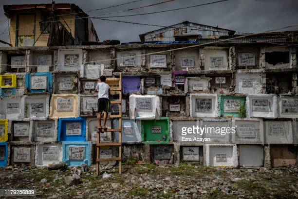 Filipino uses a ladder to visit the grave of his departed loved one at a public cemetery during All Saints' Day on November 1 2019 in Manila...