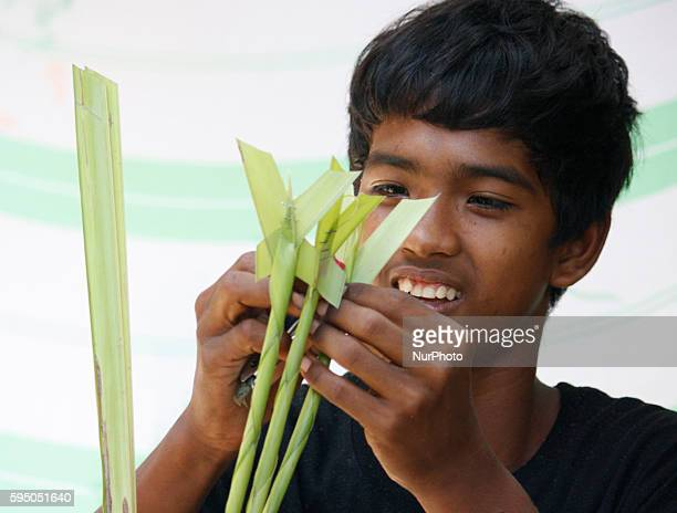 A Filipino vendor weaves palm leaves on March 18 2016 in Manila Philippines in preparation for Palm Sunday The celebration falls on a Sunday before...