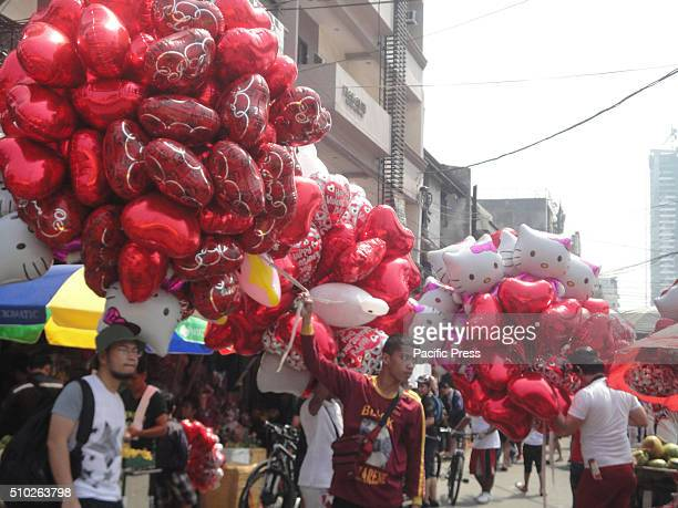 Filipino vendors sell heartshaped balloons at the Dangwa flower market in Manila Philippines on Valentine's Day Valentines Day is celebrated on...
