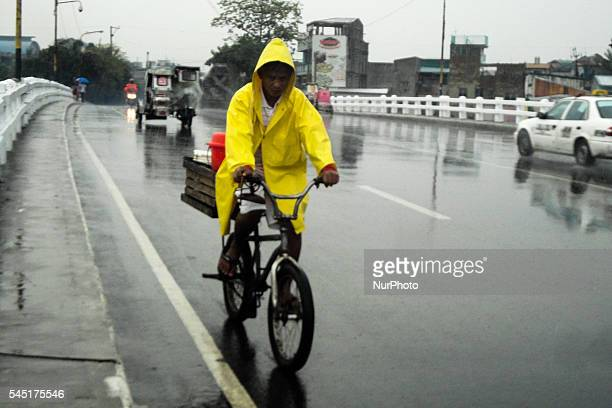 Filipino wearing a raincoat rides a bike on Tuesday, 5 July 2016 in Navotas City, north of Manila, Philippines. Tropical Storm Nepartak will not make...
