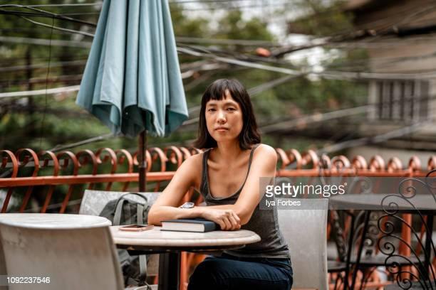 filipino woman at a cafe - literatur stock-fotos und bilder