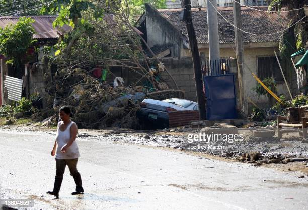 Filipino woman crosses the road of a village hit by floods following a recent typhoon on December 21 2011 in Cagayan de Oro Mindanao Philippines...