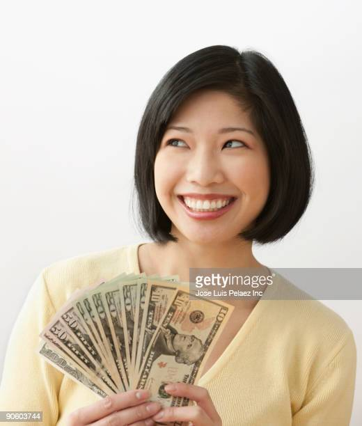 filipino woman holding money and smiling - nota de cinquenta dólares americanos - fotografias e filmes do acervo