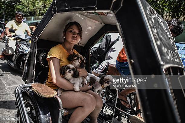 Filipino woman holds her puppies while riding in a traditional tricycle taxi ahead of the presidential and vice presidential elections in Tondo...