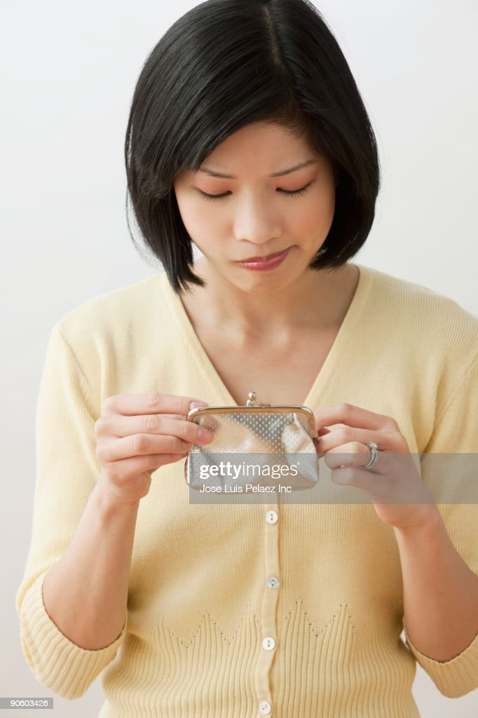 Filipino woman looking into wallet and making a face : Stock Photo