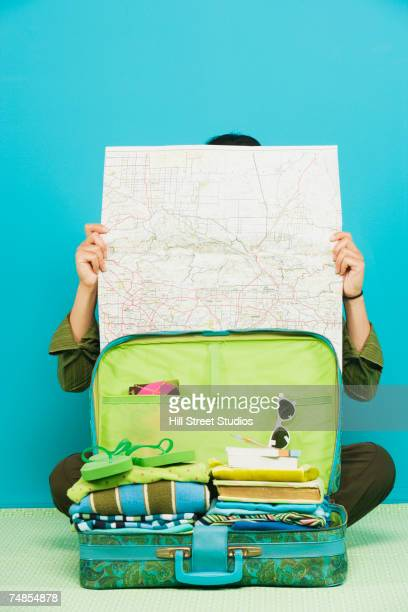 Filipino woman reading map next to suitcase