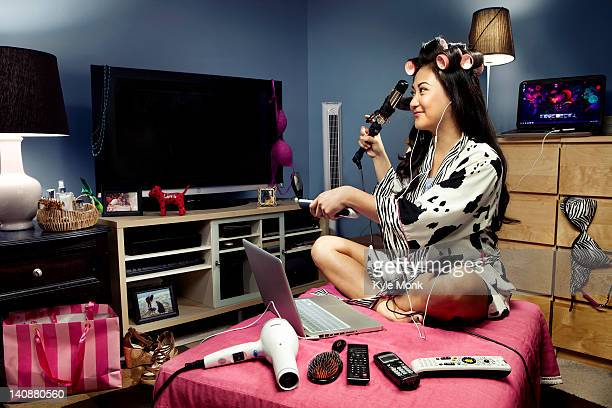 filipino woman surrounded by gadgets curling her hair - filipino ethnicity and female not male stock pictures, royalty-free photos & images