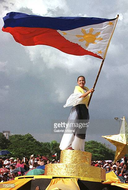 Filipino woman waves a national flag during the 104th independence day from Spain celebrations June 12 2002 in Manila Phillippines President Gloria...