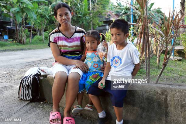 filipino woman with two children sits on a stone wall - editorial stock pictures, royalty-free photos & images