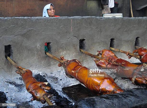 Filipino worker looks on as whole pigs are roasted in bamboo rotisseries in suburban Quezon City east of Manila Philippines Roasted pig locally...