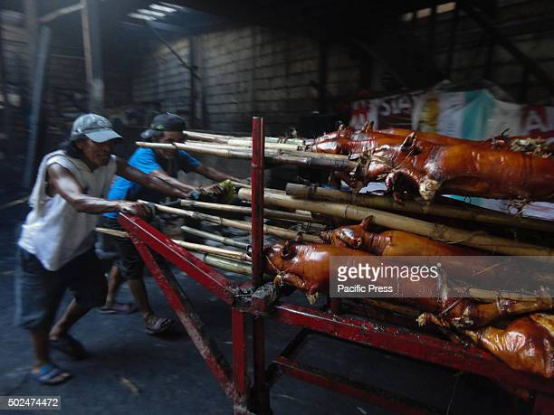 Filipino workers carry roasted pig to a nearby restaurant at suburban Quezon City east of Manila Philippines Roasted pig locally called lechong baboy...