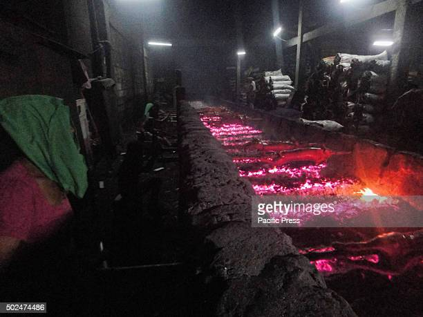 Filipino workers handle roasted pig cooked in bamboo rotiserries at suburban Quezon City east of Manila Philippines Roasted pig locally called...