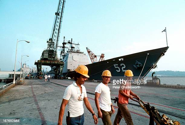 Filipino workers walk in front of a United States navy warship which is moored on the dock at Subic Bay, one of the United States military bases in...