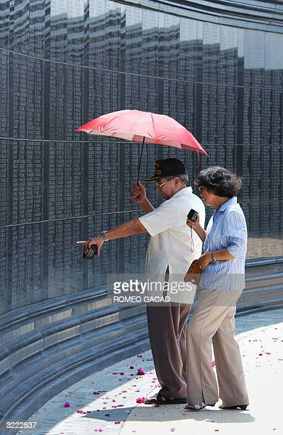Filipino World War II veteran and survivor of the Bataan death march Virgilio Gonzalez accompanied by his wife Caridad Gonzalez look at the names of...