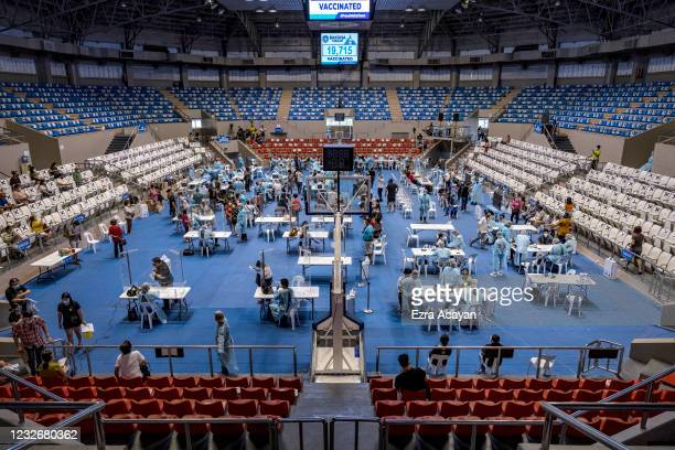Filipinos are administered with Russian Sputnik V COVID-19 vaccine at a sports arena on May 4, 2021 in Makati, Metro Manila, Philippines. The...