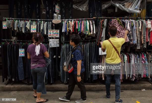 Filipinos check used clothing at an outdoor rummage store in Manila Philippines on Wednesday July 12 2017