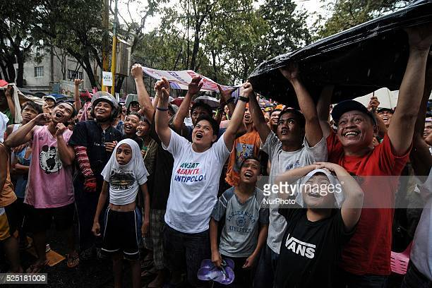 Filipinos cheer despite of a sudden downpour during a public live screening of Manny Pacquiao's match against Brandon Rios in Marikina city east of...