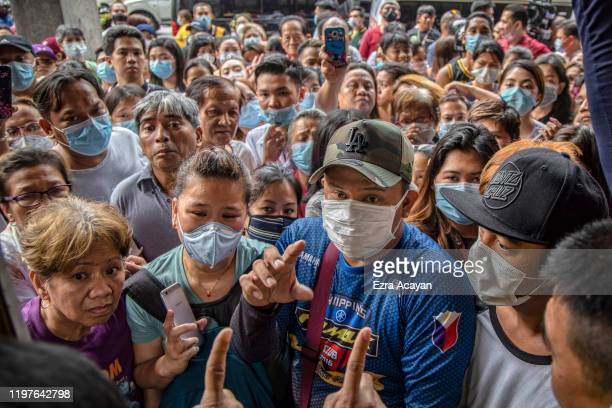 Filipinos hoping to buy face masks crowd outside a medical supply shop that was raided by police for allegedly hoarding and overpricing the masks, as...
