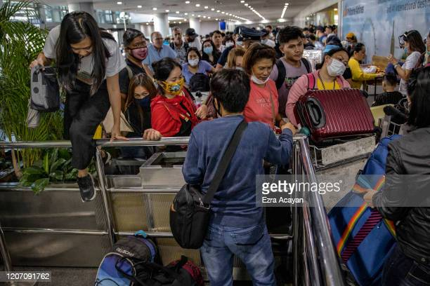 Filipinos hoping to get on flights out of Manila hours before it is placed on lockdown queue at Ninoy Aquino International Airport on March 14, 2020...