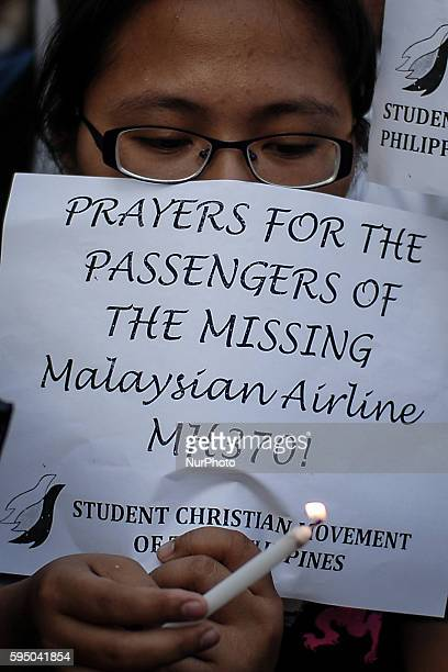 Filipinos light candles during a vigil for the missing passengers of the Malaysia Airlines MH370 in Manila Philippines March 13 2014 Officials have...