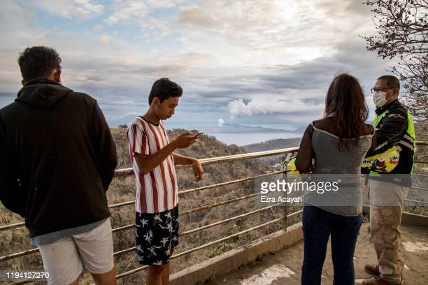 Filipinos look on as Taal Volcano spews ash on January 17 2020 in Tagaytay city Cavite province Philippines The Philippine Institute of of...