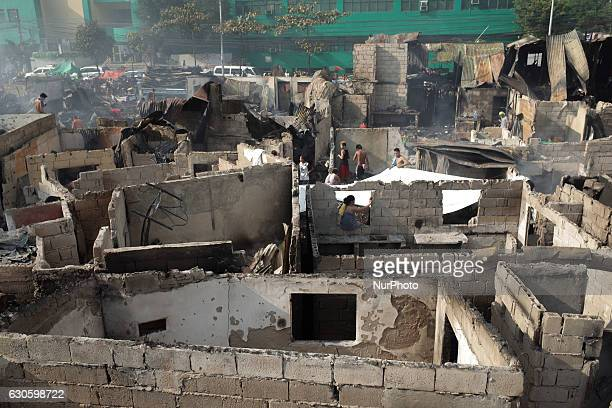 Filipinos looks for salvageable materials following a fire at an informal settler colony in Quezon City east of Manila Philippines on Wednesday...